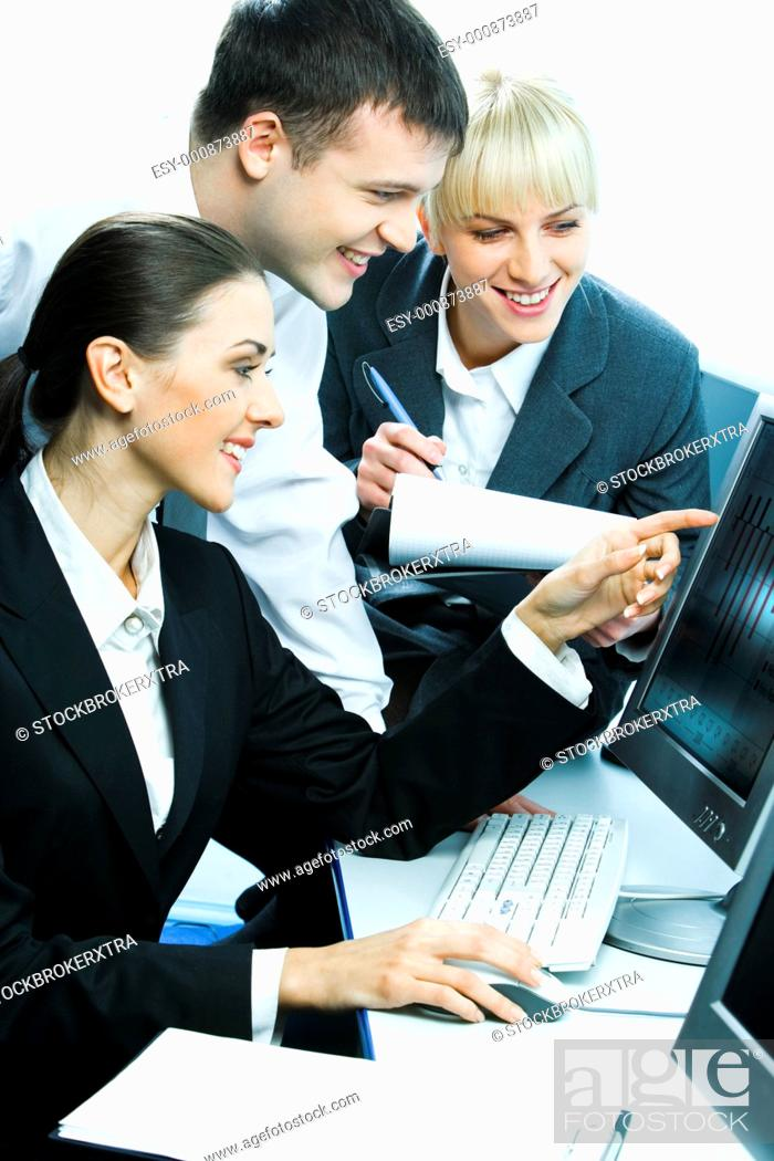 Stock Photo: Photo of three smiling students sitting at the desk before the computer looking at its monitor while a girl writing something down.