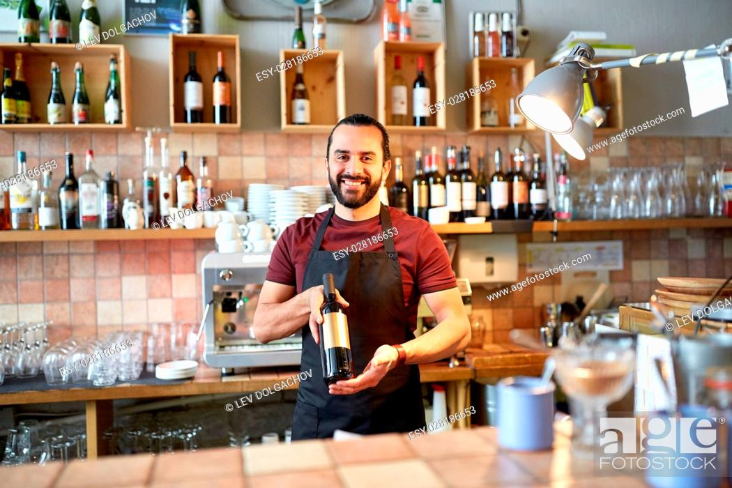 Stock Photo: small business, alcohol drinks, people and service concept - happy man or waiter with bottle of red wine at bar.