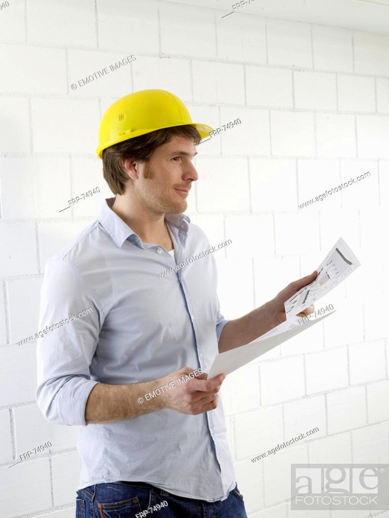 Stock Photo: Man wearing a helmet with construction plans.