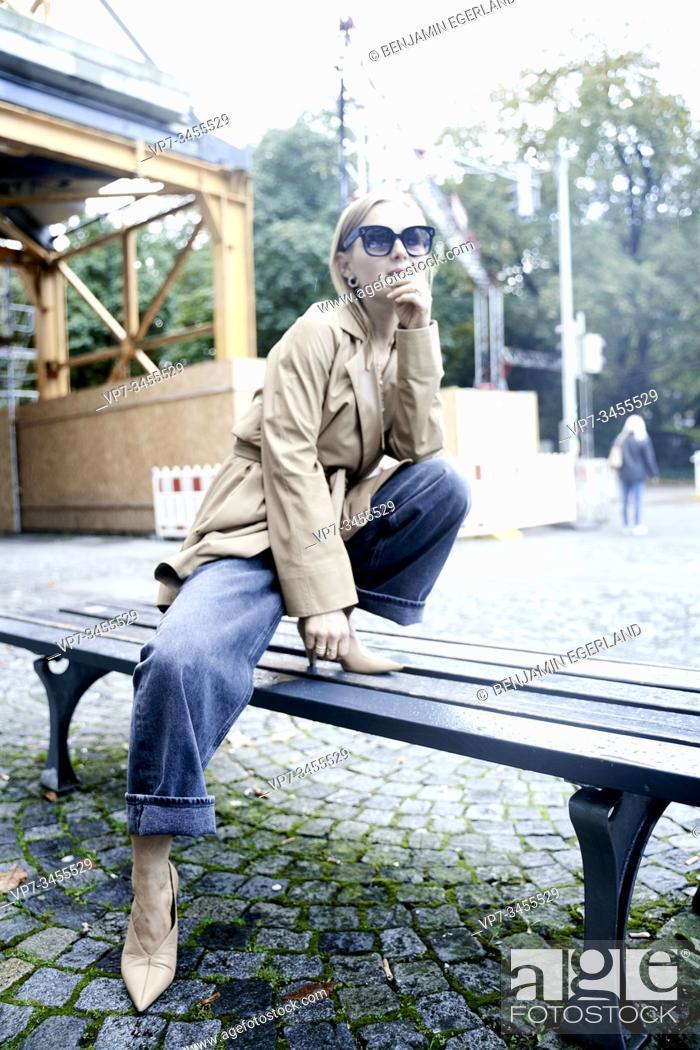 Stock Photo: Fashionable woman on bench. Munich, Germany.