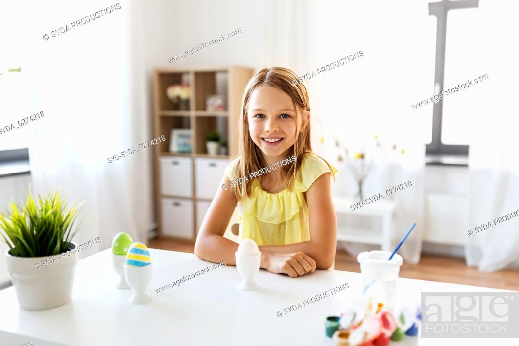 Stock Photo: happy girl with easter eggs and colors at home.