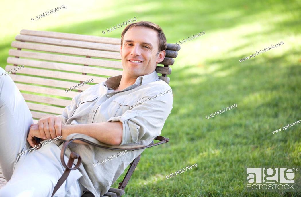 Stock Photo: Portrait of confident man sitting on park bench.