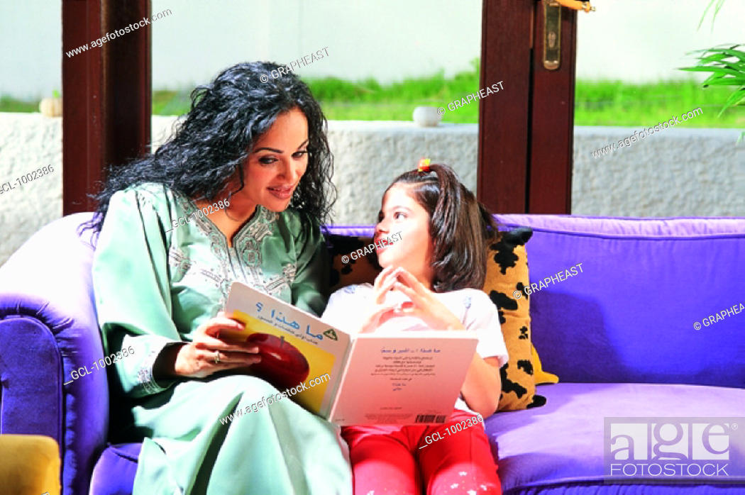 Stock Photo: Mother and daughter reading in a book.