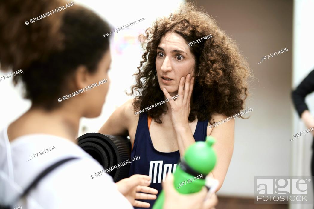 Stock Photo: apprehensive woman listening to story of friend in fitness studio.