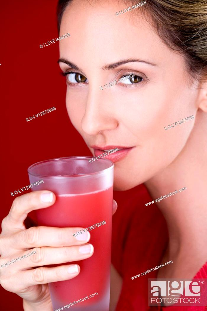 Stock Photo: A mid adult woman drinking a glass of fruit juice.
