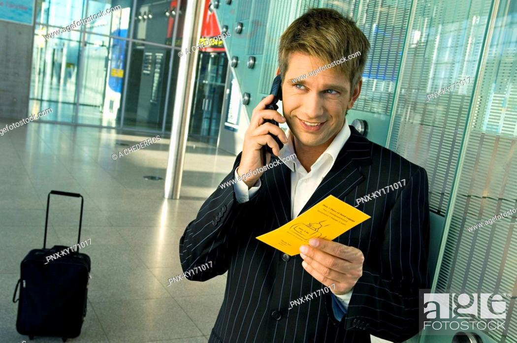 Stock Photo: Businessman holding an airplane ticket and talking on a mobile phone at an airport.