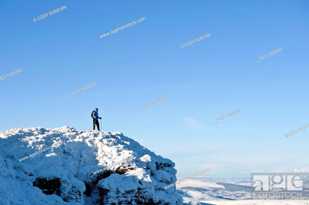 Stock Photo: Female hiker stands on summit of Corn Du in winter, Brecon Beacons nationl park, Wales.
