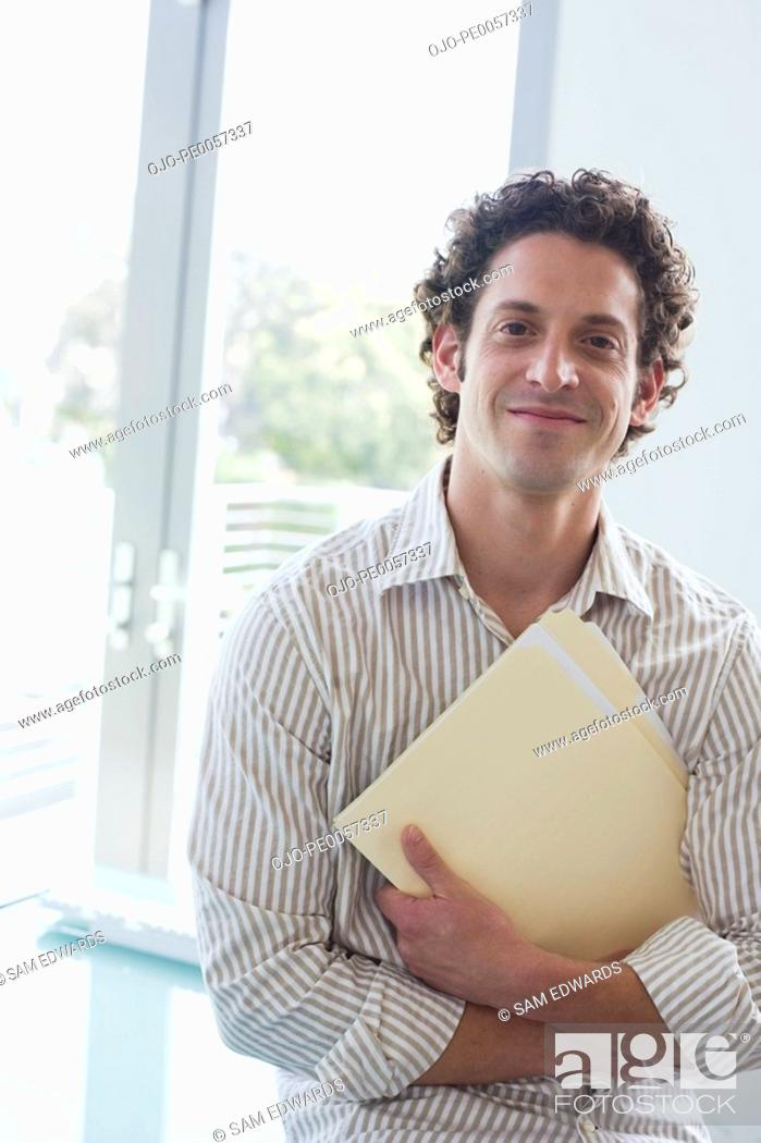 Stock Photo: Businessman holding folder in arms in office.