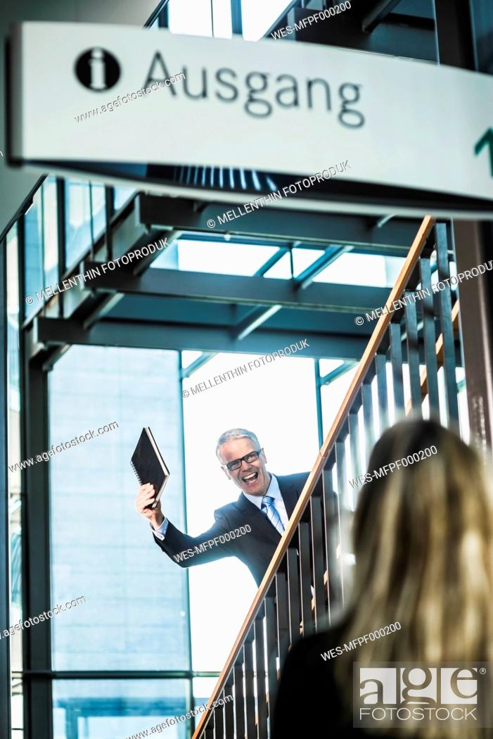 Stock Photo: Germany, Stuttgart, Businessman showing diary to woman on stairs of office building.