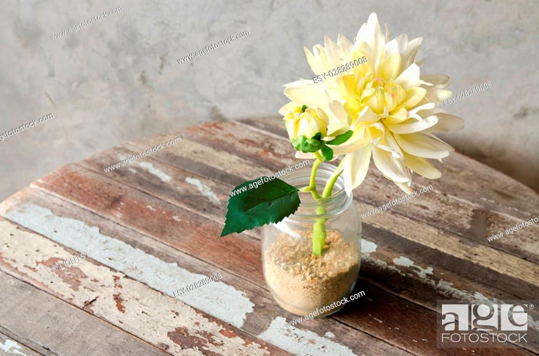 Stock Photo: Yellow Artificial Flower decorated on wooden table.