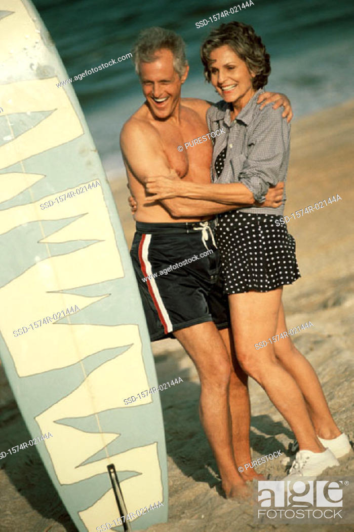 Stock Photo: Senior couple embracing each other on the beach standing beside a surfboard.