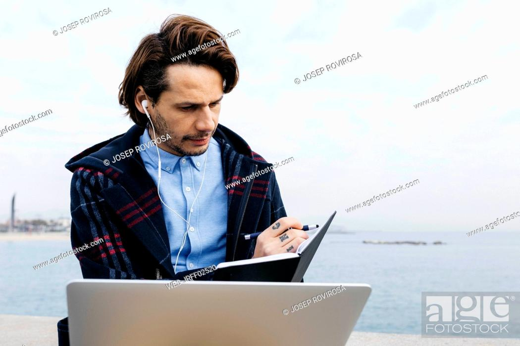 Stock Photo: Spain, Barcelona, man sitting at the sea working with laptop and notebook.