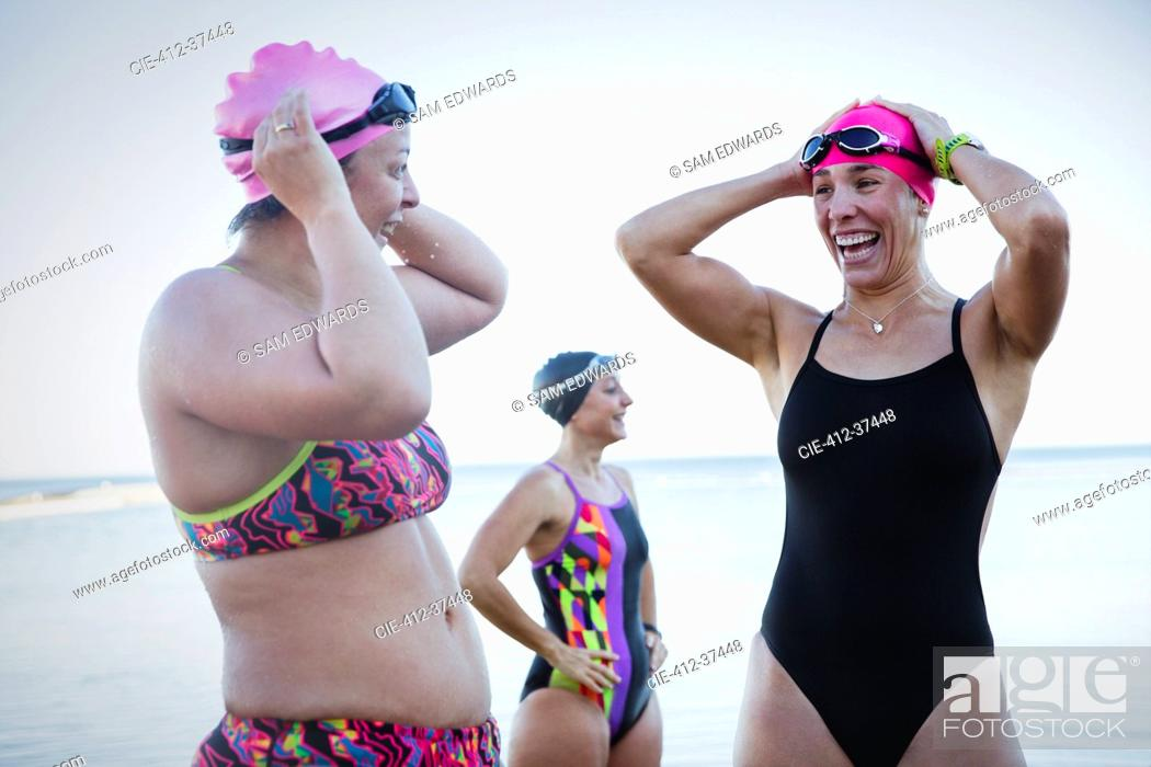 Stock Photo: Smiling female open water swimmers adjusting swimming caps at ocean.