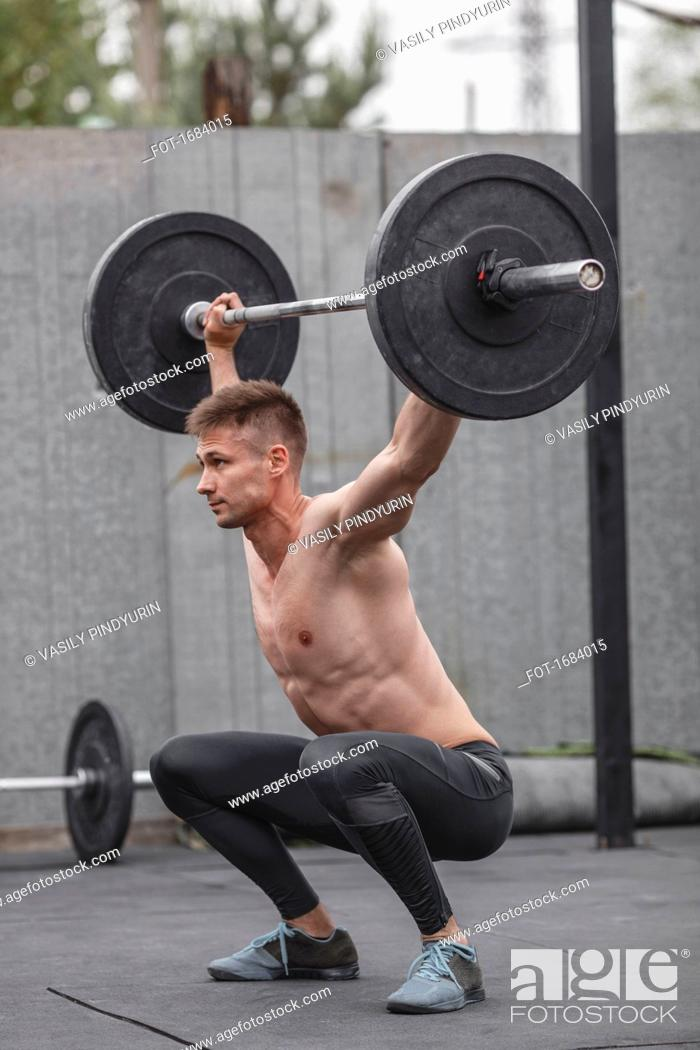 Stock Photo: Shirtless male athlete lifting barbell during crossfit training.