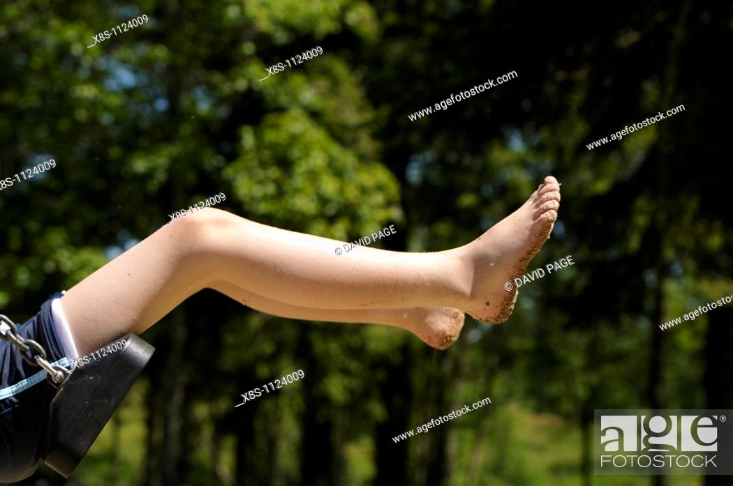 Stock Photo: 10 year old boy swinging on a playground swing.