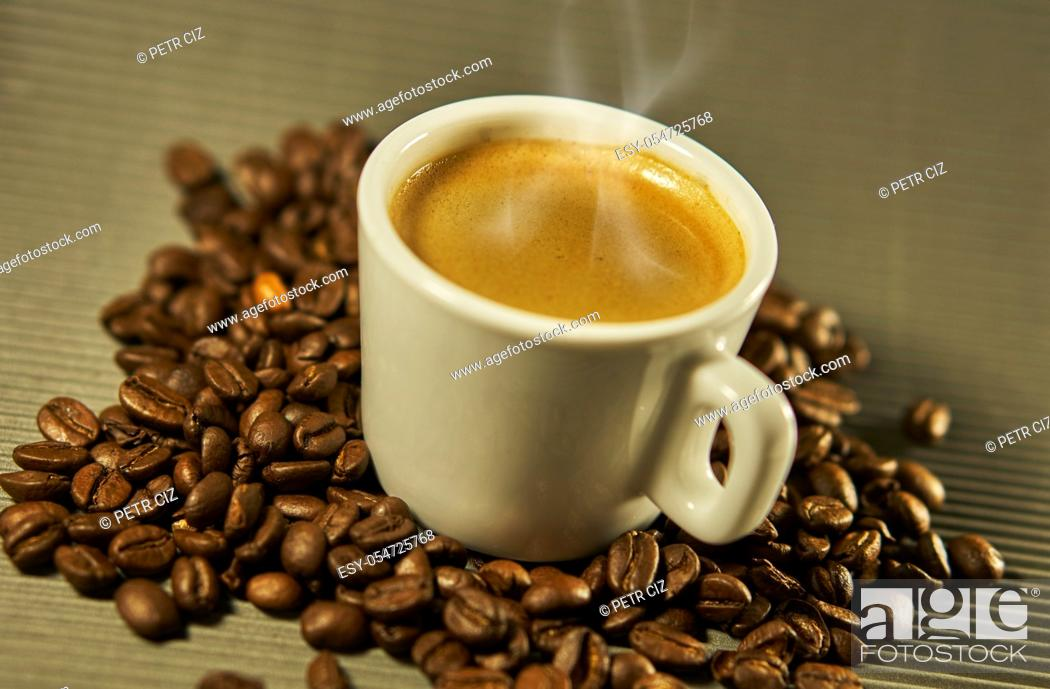 Stock Photo: Hot espresso coffee between coffee beans.
