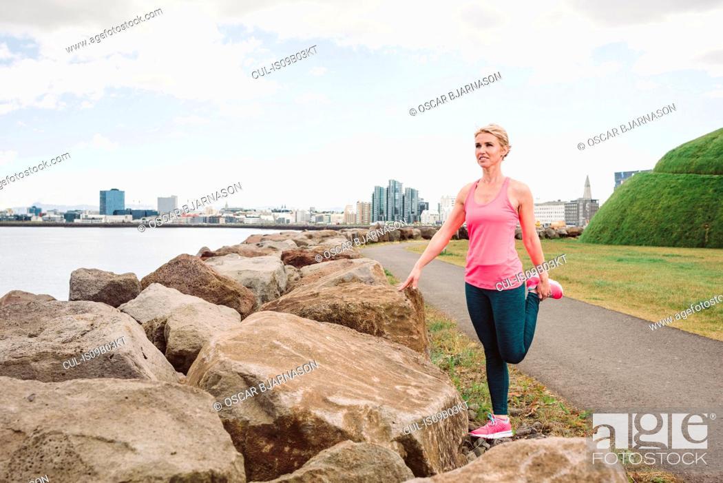 Stock Photo: Female runner stretching leg waterfront, Reykjavik, Iceland.