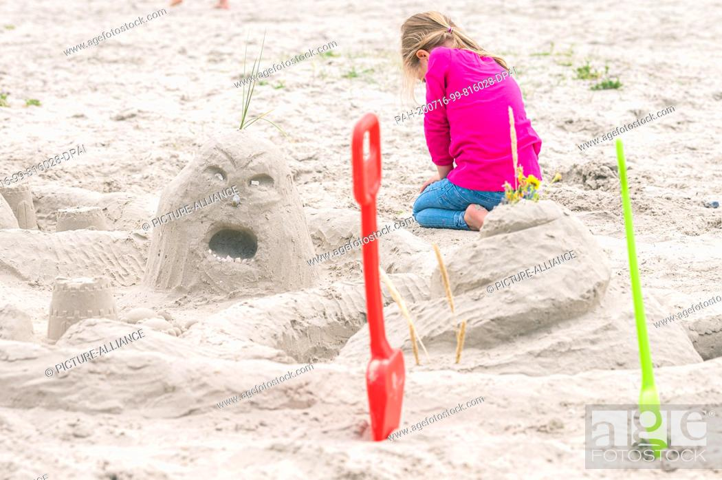 Photo de stock: 15 July 2020, Lower Saxony, Norddeich: A young girl is sitting behind a sand castle on the beach of Norddeich. Photo: Mohssen Assanimoghaddam/dpa.