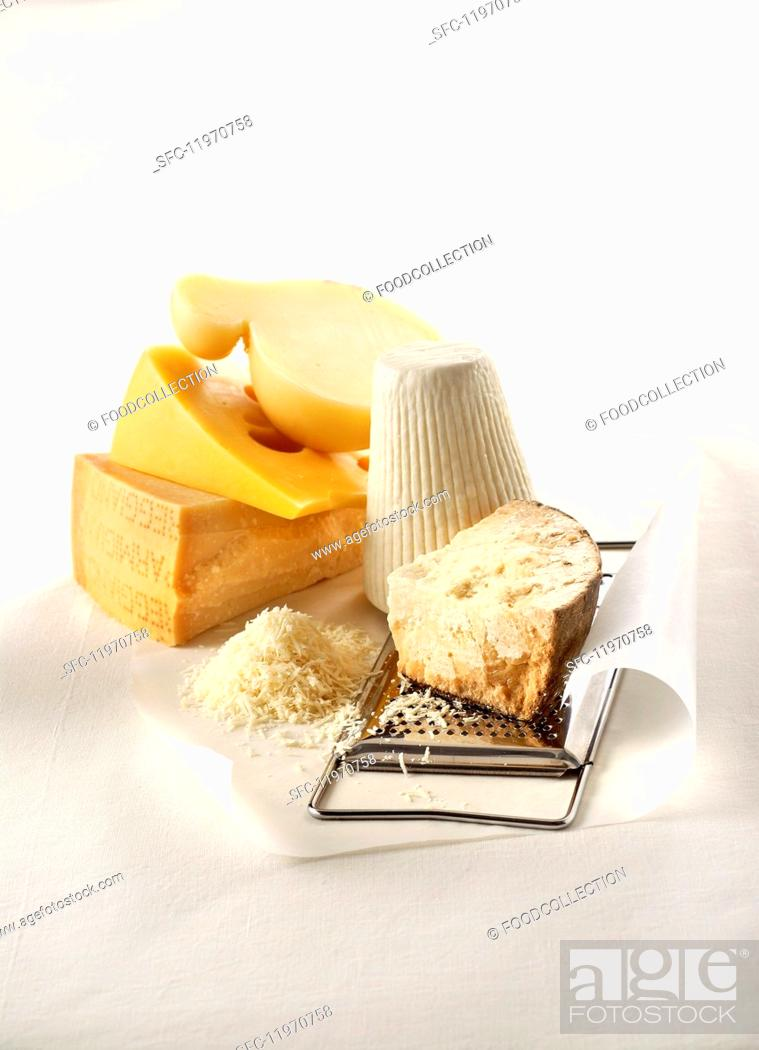 Stock Photo: Five grateable hard cheeses, grated cheese and a cheese grater.