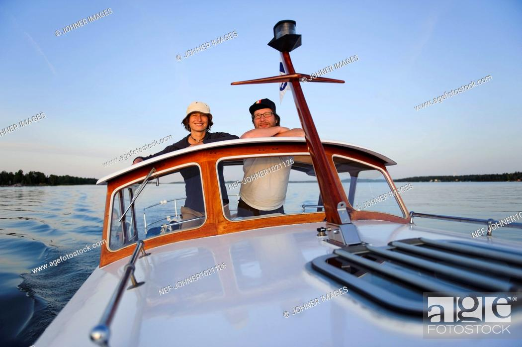 Stock Photo: Mature couple travelling in motorboat, portrait.