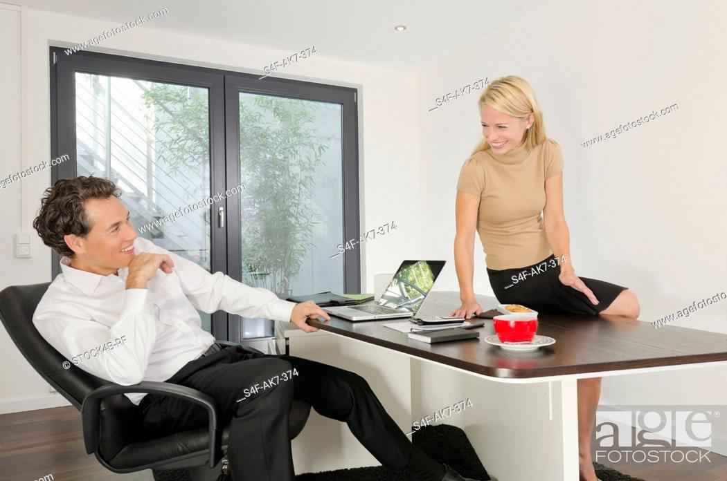 Stock Photo: Businessman and businesswoman in office smiling at each other.