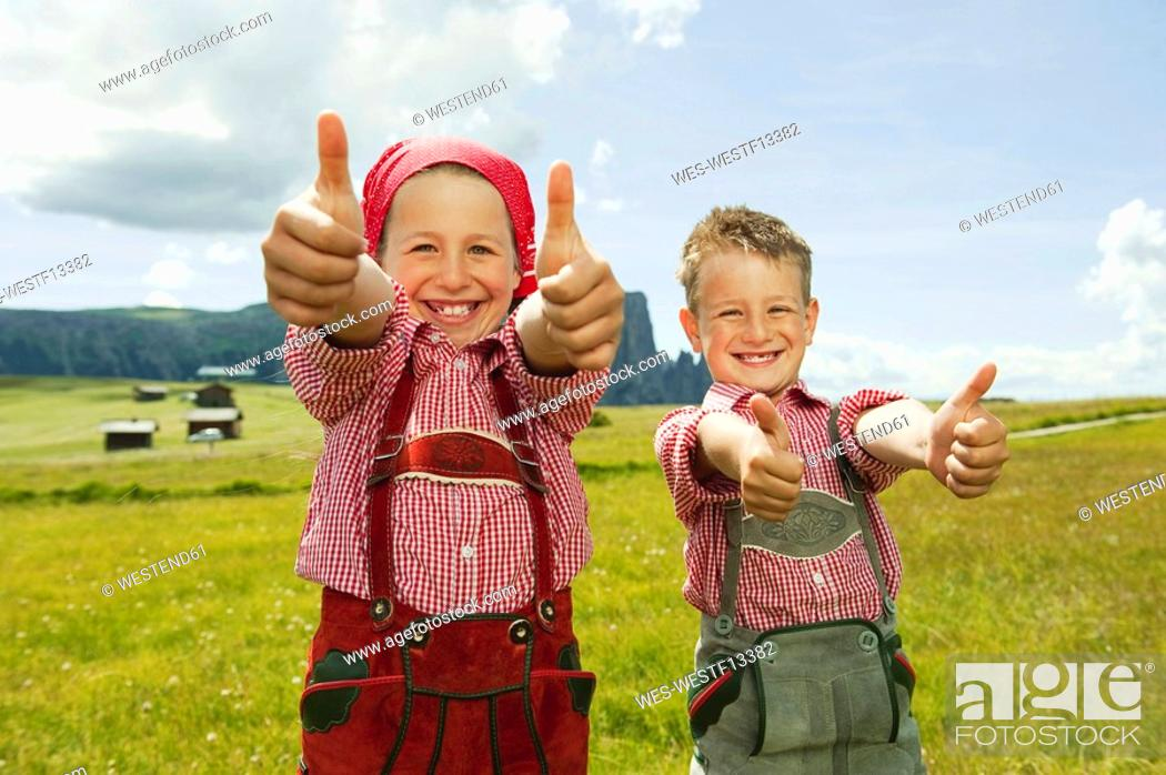 Stock Photo: Italy, Seiseralm, Boy 6-7 and girl 8-9 in field, thumbs up, smiling, portrait, close-up.