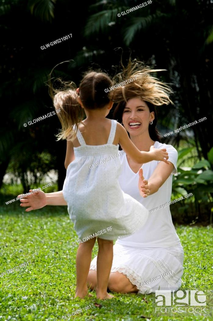 Stock Photo: Young woman playing with her daughter in a park.