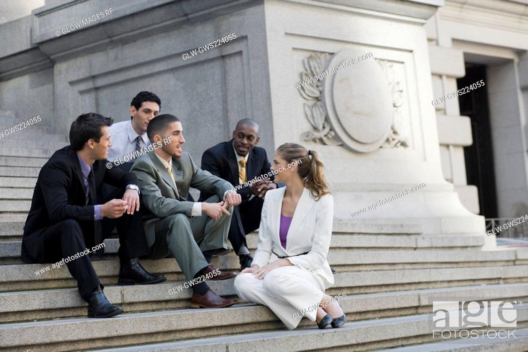 Stock Photo: Four businessmen and a businesswoman sitting on steps and discussing.