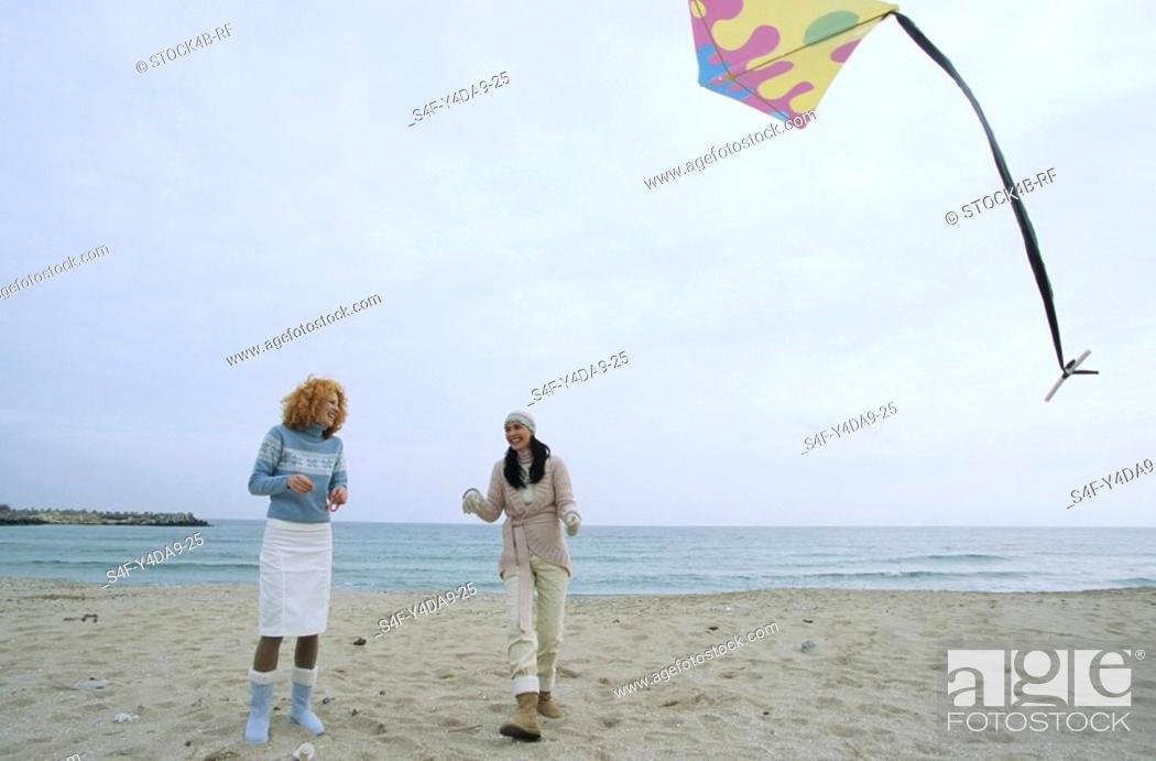 Stock Photo: Two female Friends laughing while a Kite flies by - Friendship - Fun - Trip - Season - Beach.