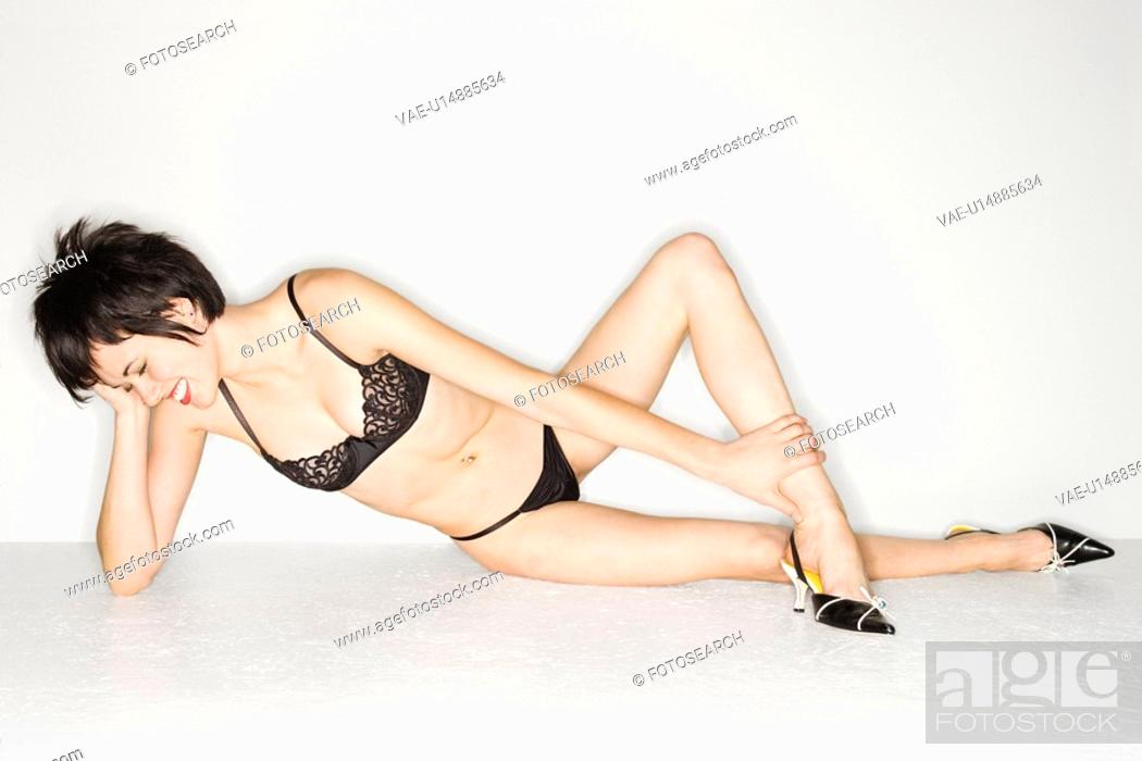 Stock Photo: Young sexy Caucasian woman wearing black lace underwear lying on the floor and laughing.