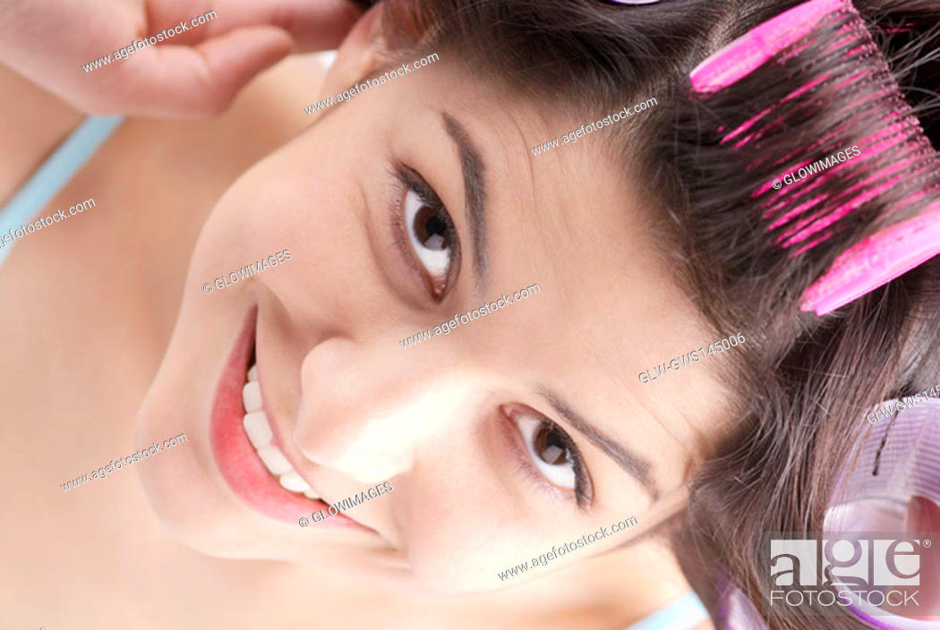 Stock Photo: High angle view of a young woman putting on hair curlers and smiling.