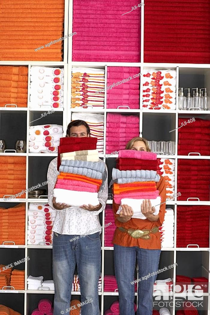 Stock Photo: Couple shopping in department store, holding two piles of towels beside shelf, faces obscured.