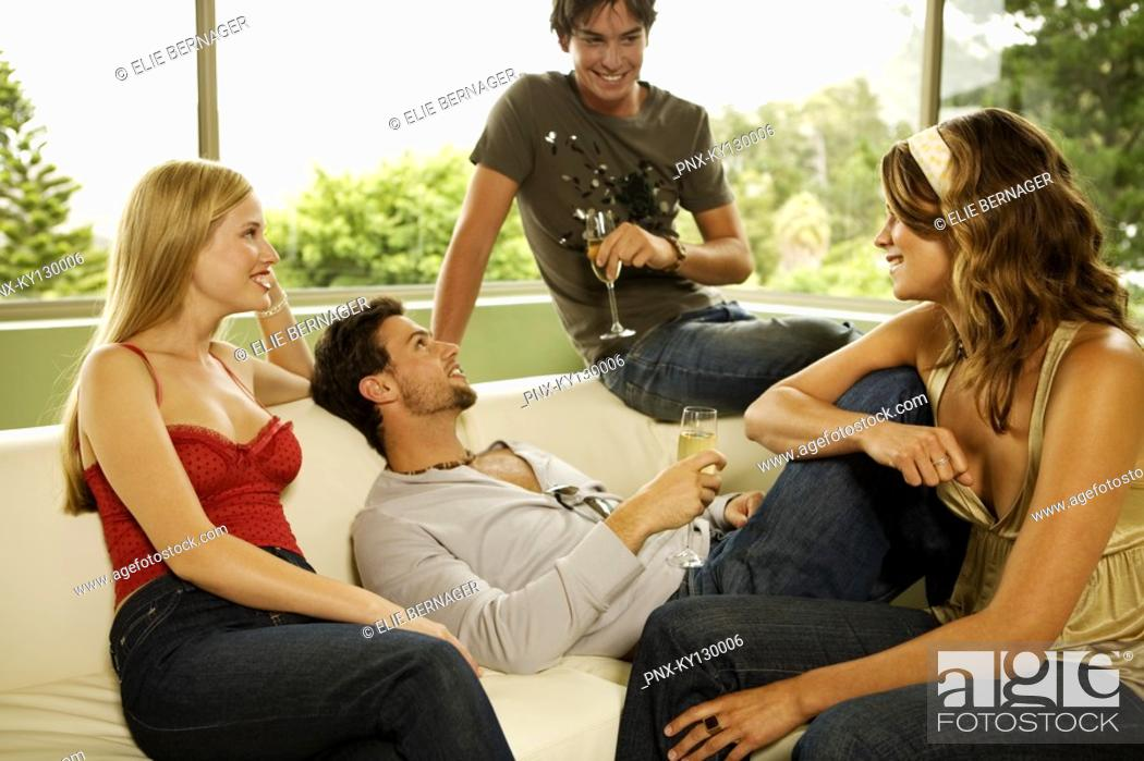 Stock Photo: 2 young smiling couples drinking champagne, sitting in sofa.
