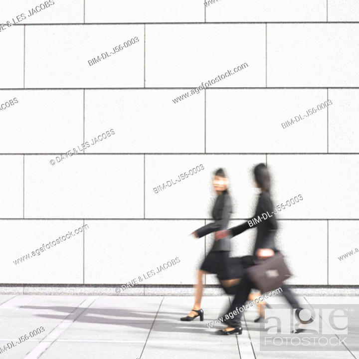 Stock Photo: Blurred image of two businesswomen walking.