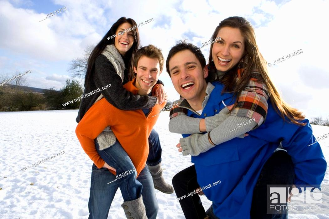 Couples giving piggyback rides in snowy field, Stock Photo