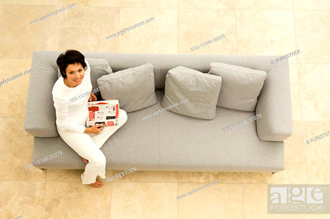 Stock Photo: Portrait of a young woman sitting on a couch and smiling.