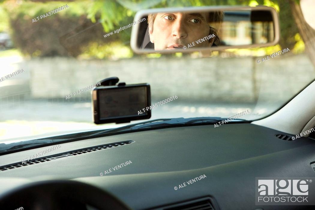 Stock Photo: Driver checking rear-view mirror.