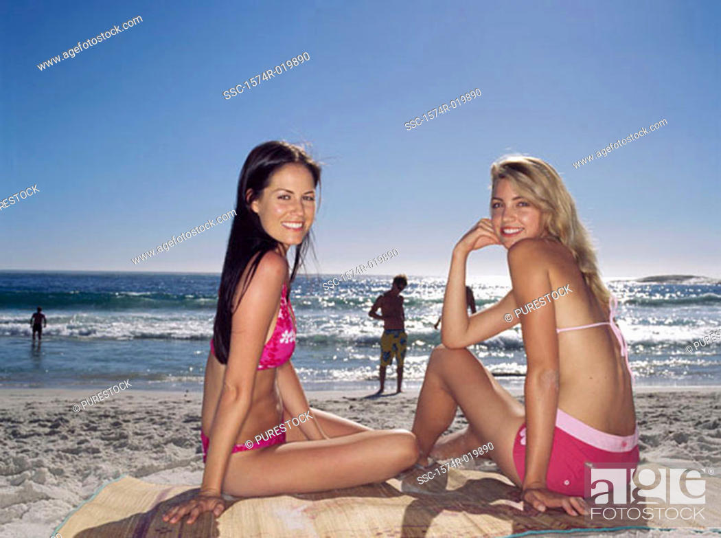 Stock Photo: Side profile of two young women sitting on the beach.