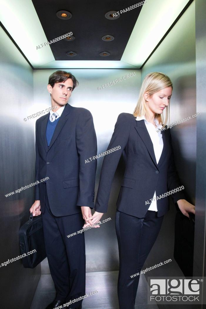 Stock Photo: Professionals holding hands in elevator.