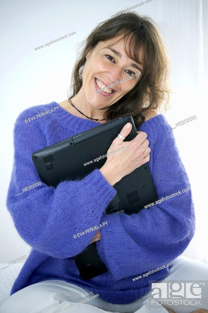 Stock Photo: Happy woman smiling and loving her computer in bed.