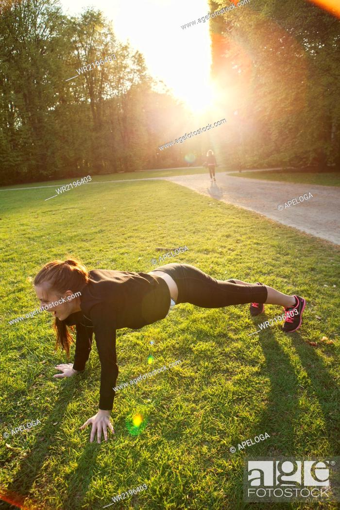 Stock Photo: Young woman doing push-ups on grassy field in park.