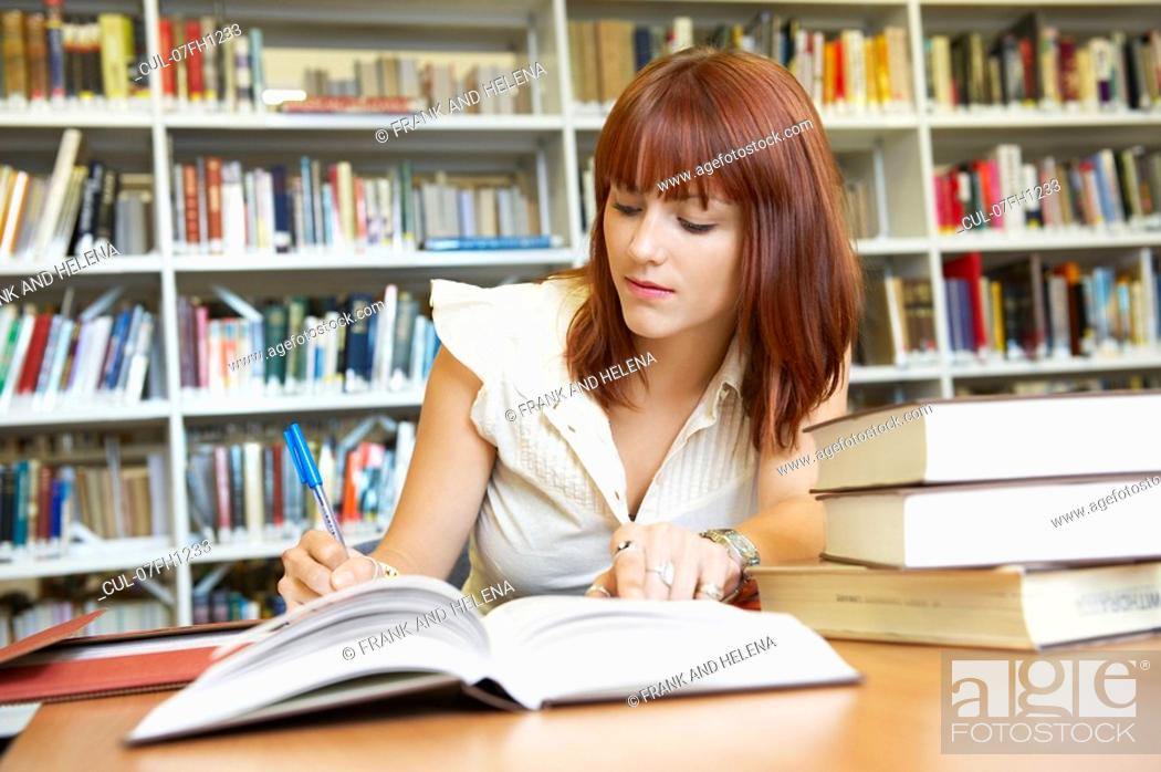 Stock Photo: Young woman working in library.