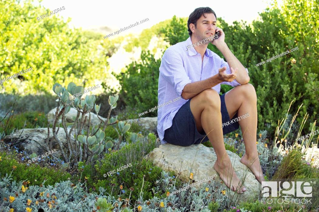 Stock Photo: Mid adult man sitting on a rock and talking on a mobile phone.
