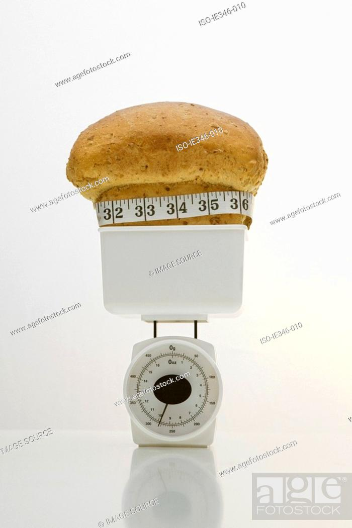 Stock Photo: A loaf of bread on weight scales.