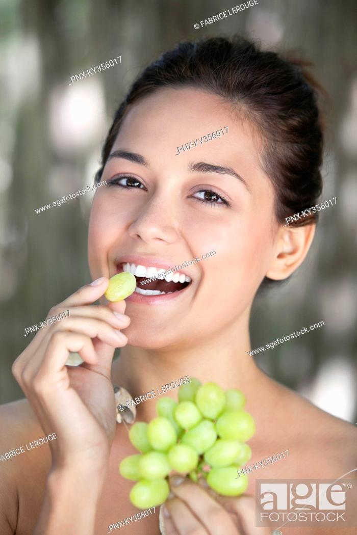 Stock Photo: Portrait of a young woman eating grapes.