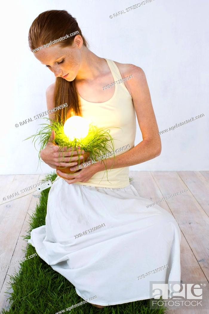 Stock Photo: woman with energy saving light bulb in plant.