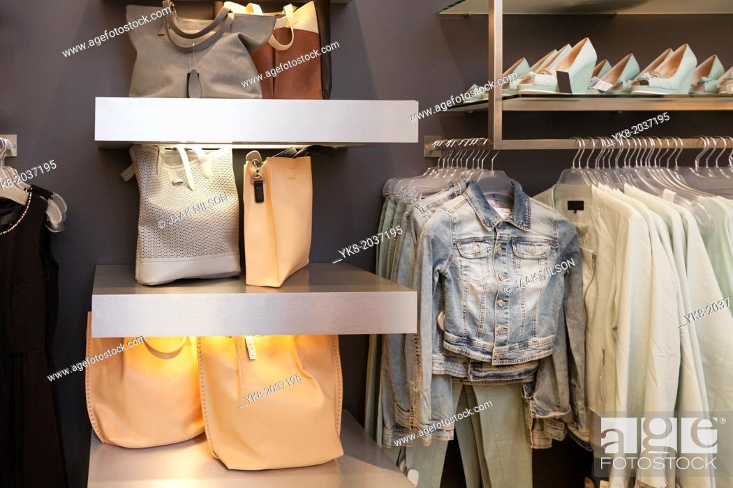 Stock Photo: Blouses, shirts and jackets hanging on rack in retail shop interior. Bags, handbags, shoulder bags on shelf.