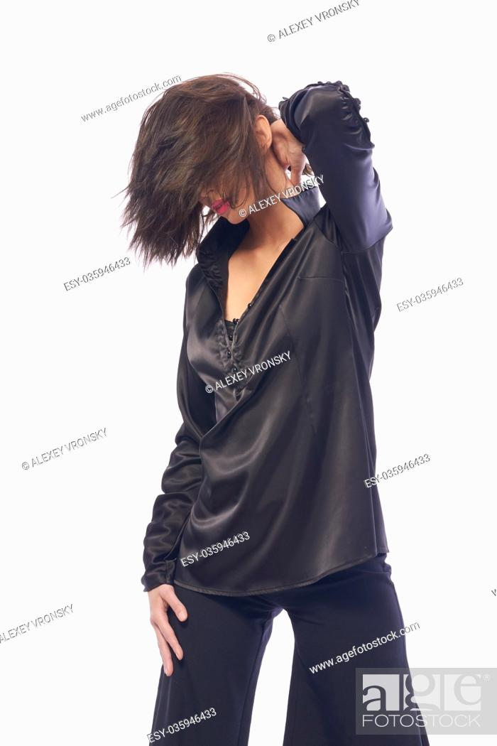 Stock Photo: Young dark-haired girl in stylish clothes posing in front of camera. The girl is very cute and has a model appearance and a good slender figure.