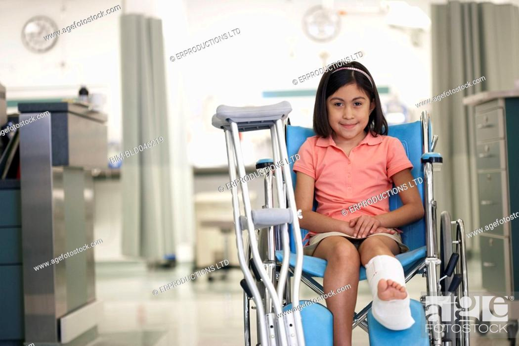 Stock Photo: Hispanic girl with cast in wheelchair.