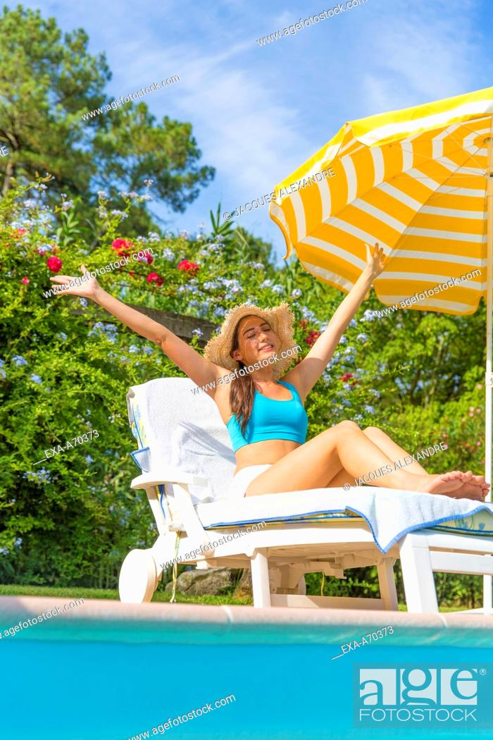 Imagen: Woman sunbathing at swimming pool.